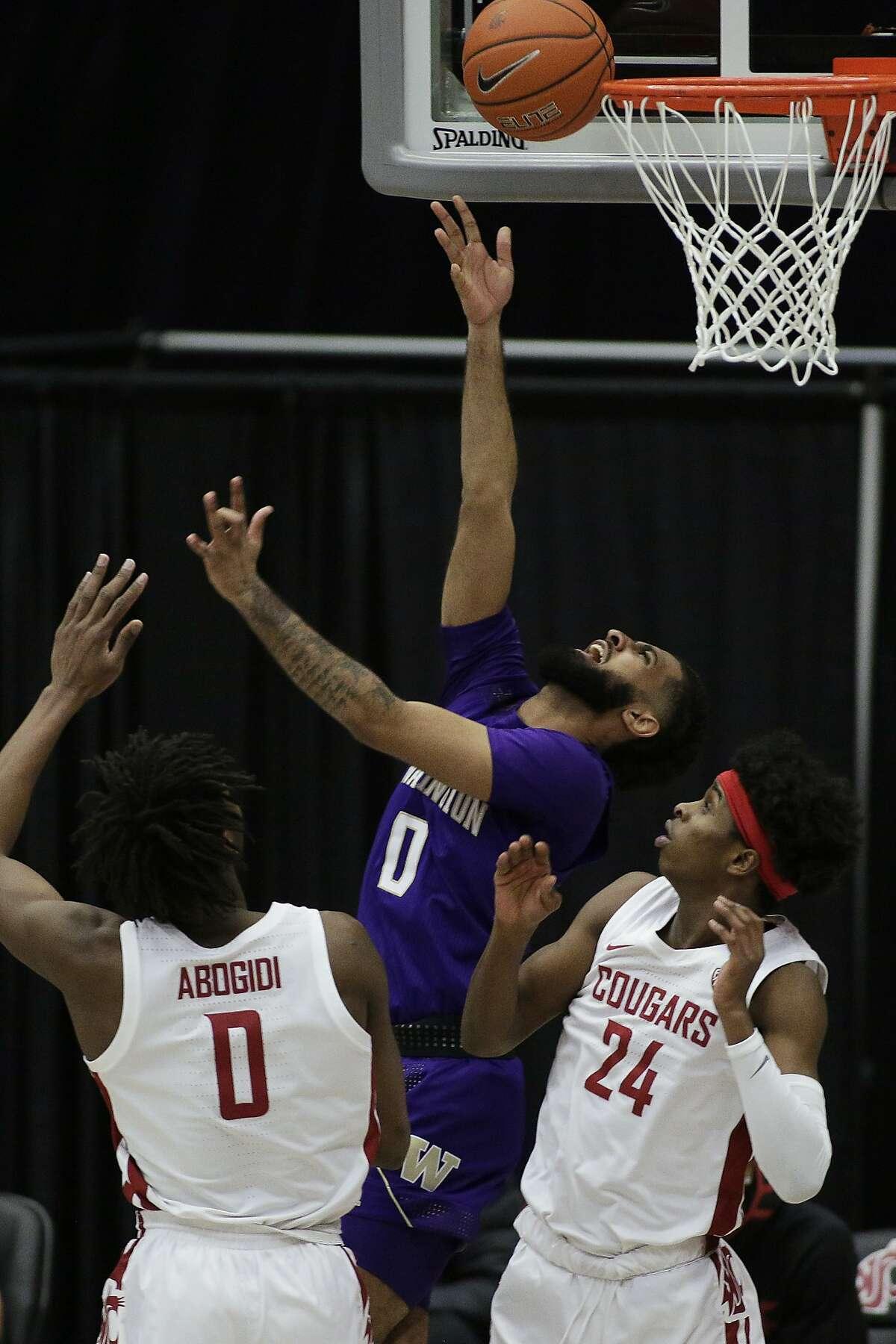 Washington's Marcus Tsohonis shoots over Washington State's Efe Abogidi and Noah Williams (24) in the first half.