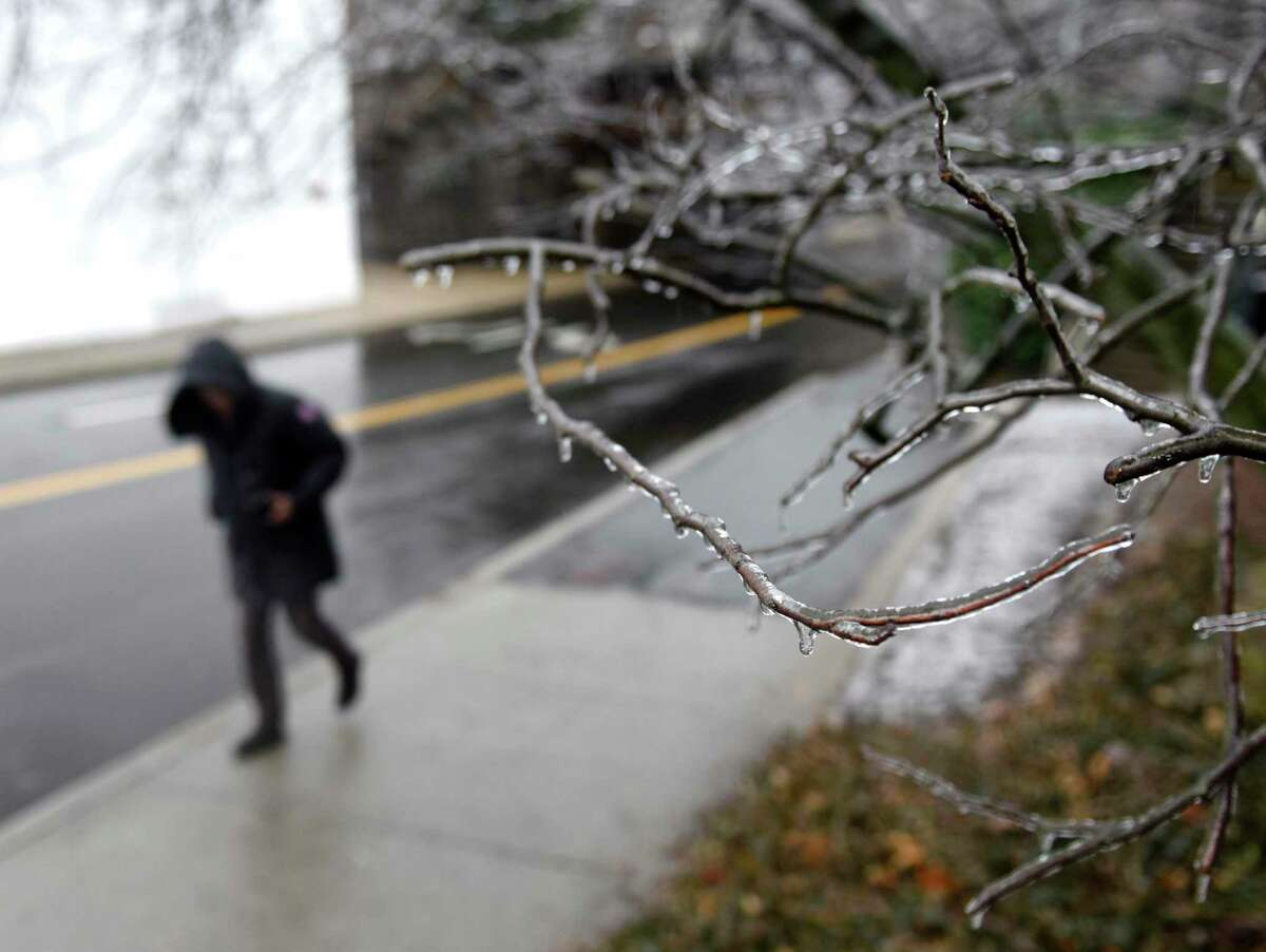 A file photo of an individual walking by an icy tree in Greenwich, Conn. Freezing rain is transitioning over to just rain Tuesday, Feb. 16, 2021.