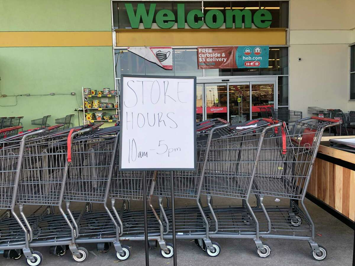 Grocery carts are lined up to block the entrance and a sign alerts shoppers to modified hours at the H-E-B Plus! February 16, 2021 in Pearland.