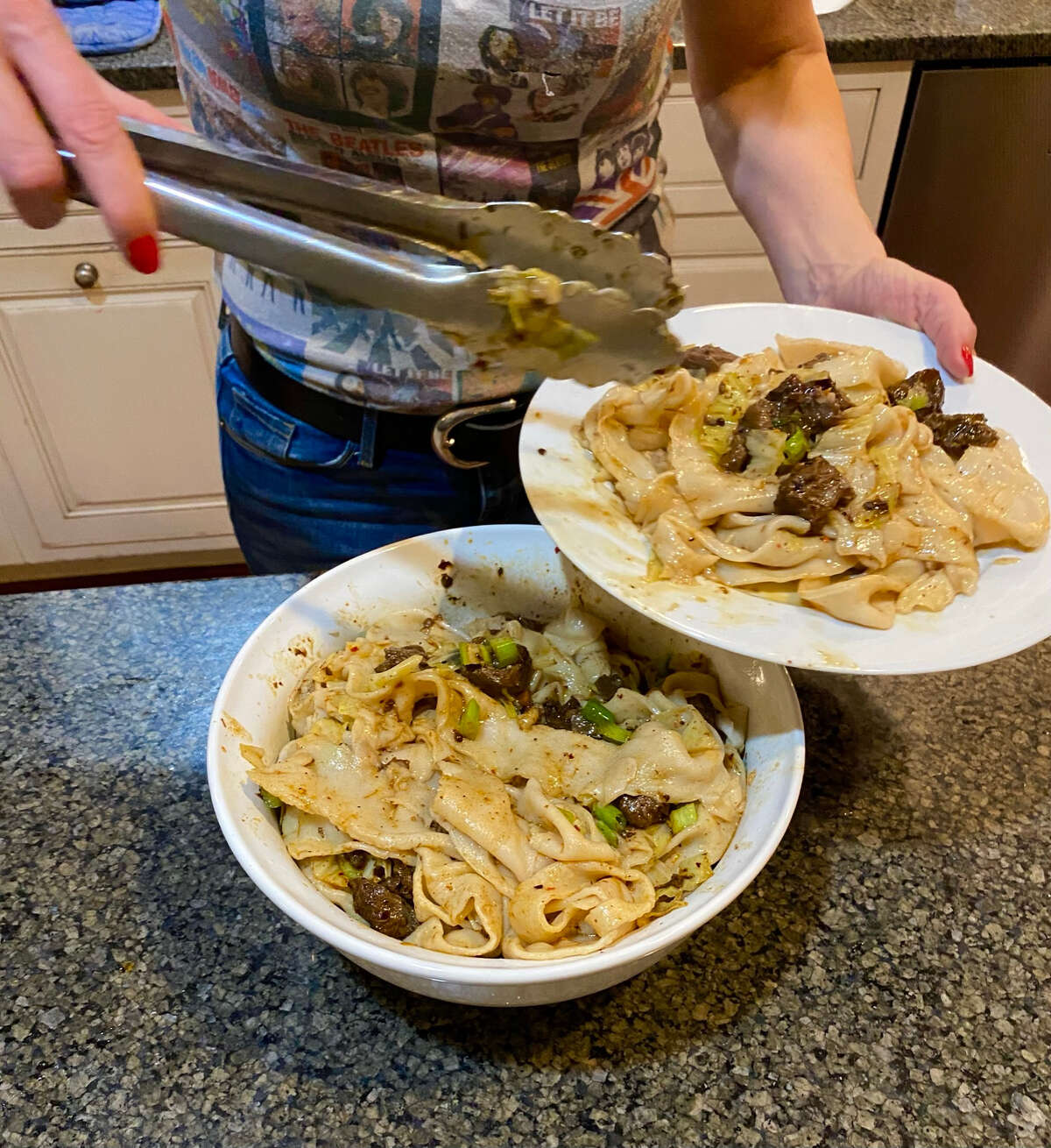 Susie Davidson Powell finishes a noodle dish with beef in a delivery meal kit from Xi'an Famous Foods in New York City. (Provided photo.)