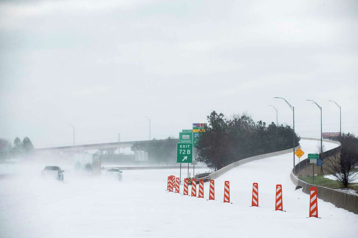 The north entrance of the Hardy Toll Road is blocked after the roadway was closed following an overnight snowfall Monday, Feb. 15, 2021 in Spring. Temperatures plunged into the teens Monday with light snow and freezing rain.