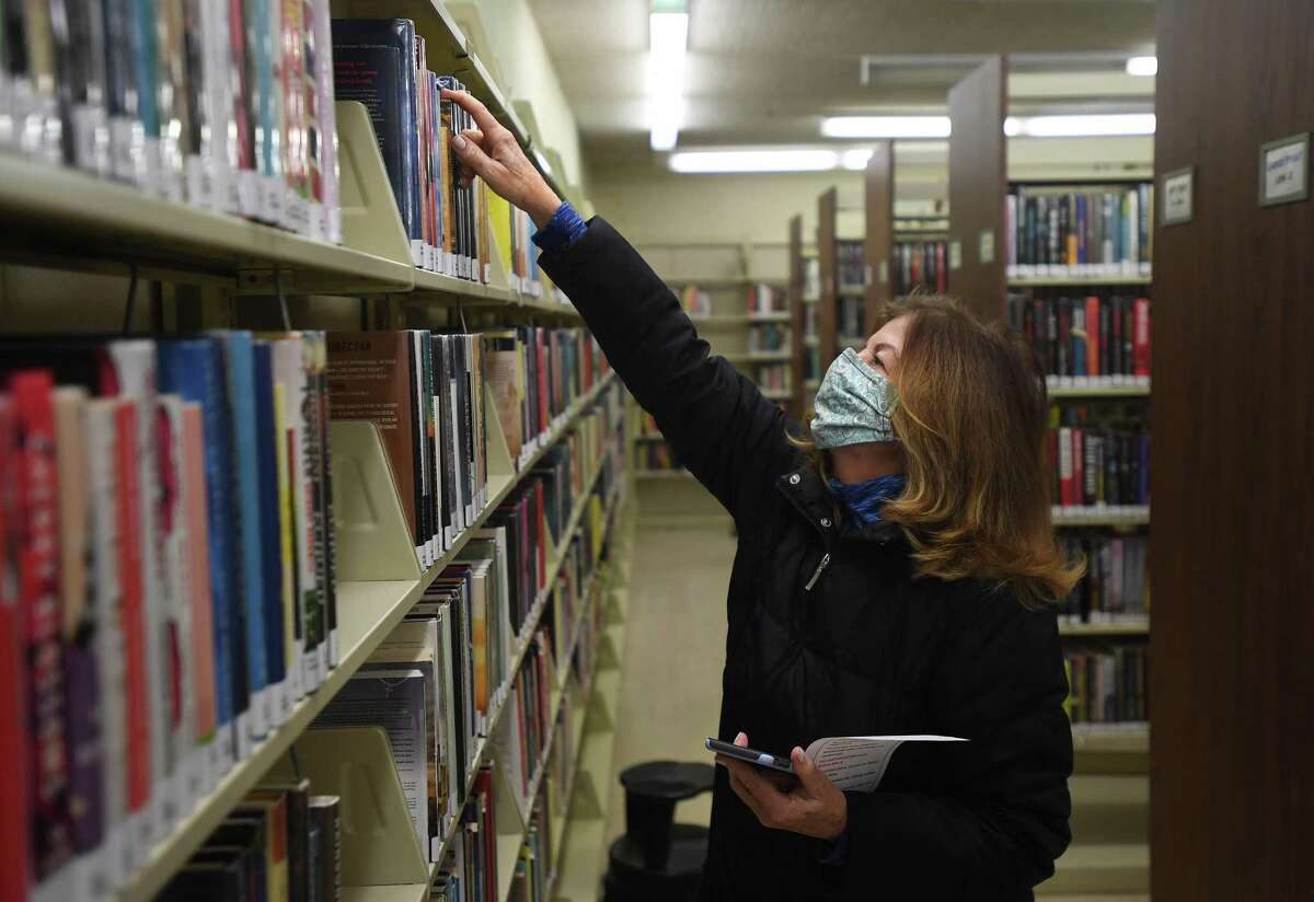 Juliann Vaughan, of Shelton, picks out a book after being the first customer through the doors during the reopening of the Plumb Memorial Library on Tuesday.