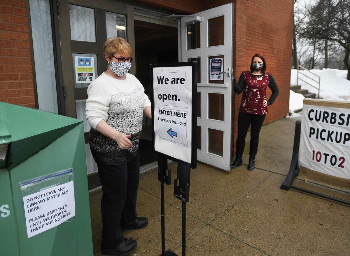 Library employees Marcia Austin, left, and Jessica Prutting open the doors for the first time in over a month during the reopening of the Plumb Memorial Library on Tuesday.