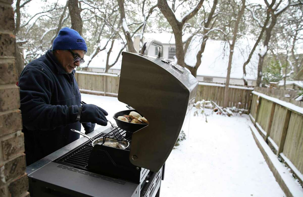 Kim Scott cooks biscuits and sausages for breakfast on his outdoor propane grill on Tuesday, Feb. 16, 2021. Kim and his wife, Clara, lost power in their house about 7 p.m. on Monday. Scott said they still managed to cook dinner last night on the grill as well. They live in a subdivision off Vance Jackson Road where according to the CPS Energy website has one of the most extensive outages in the city.