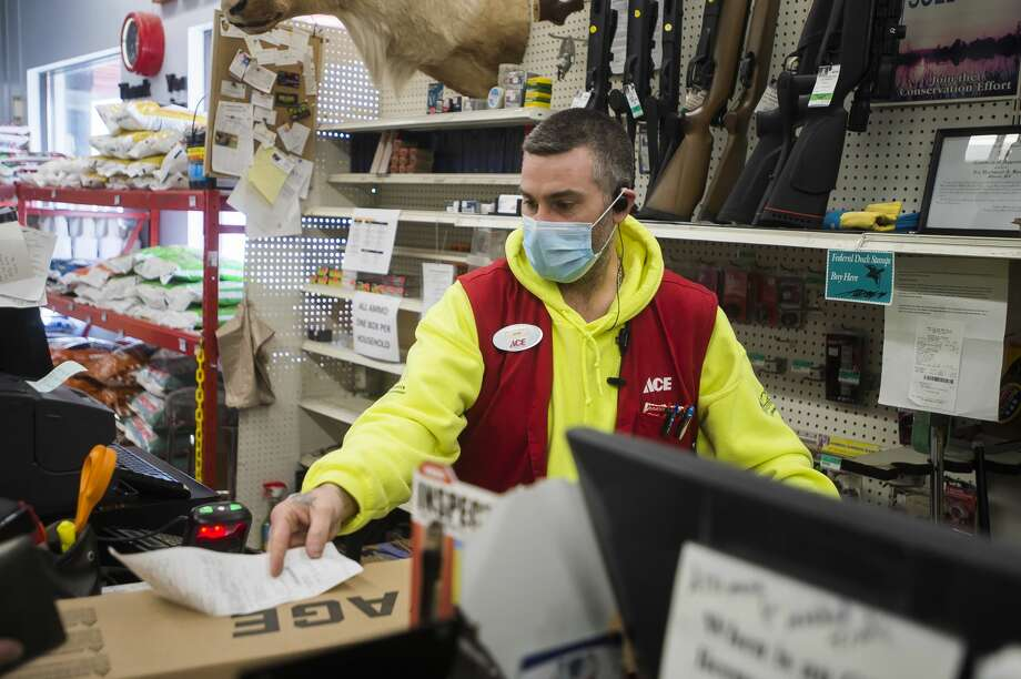 Midland Ace Hardware manager of sporting goods Jon Leiner assists a customer in purchasing a rifle Thursday, Feb. 11, 2021 at the store in Midland. (Katy Kildee/kkildee@mdn.net) Photo: (Katy Kildee/kkildee@mdn.net)