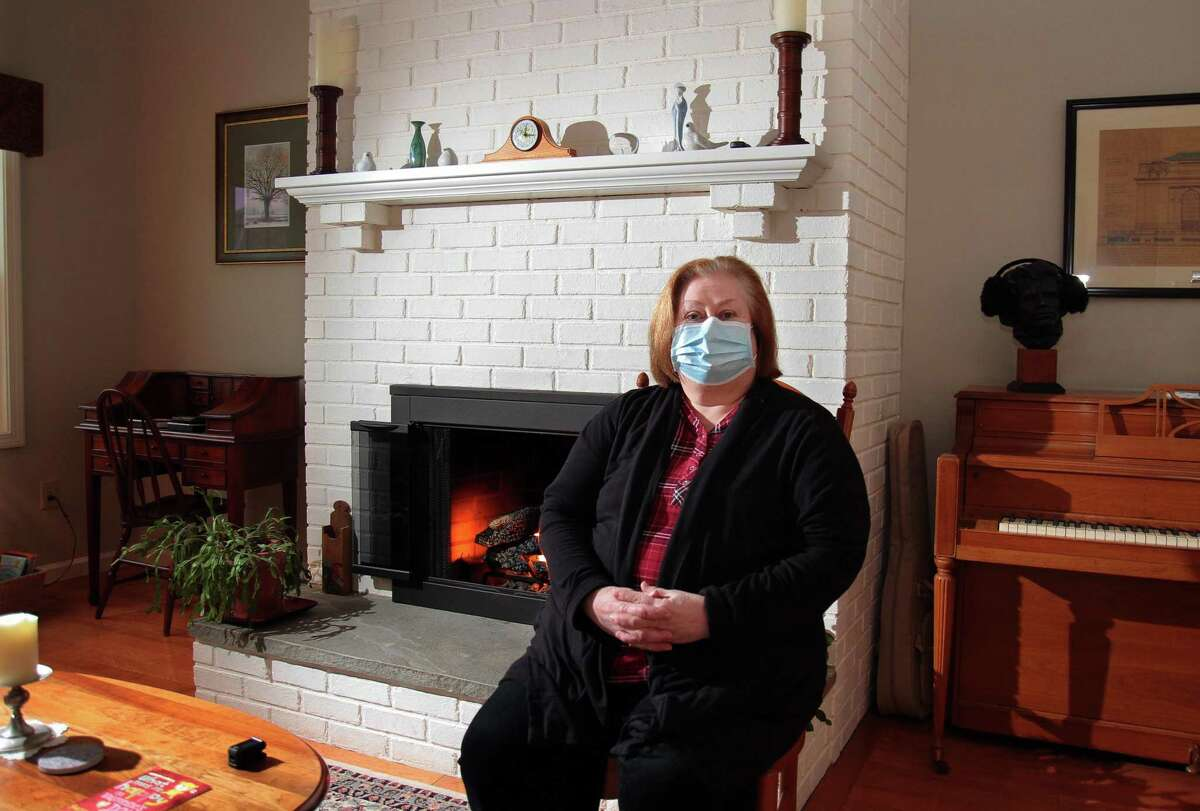 Joan Stokes, who is recovering from COVID-19, poses in her home in Woodbury on Saturday. The Shelton Library, where Stokes works as director, has been closed since several staffers tested positive, many who were hospitalized including one who died. Stokes spent 12 day in the hospital.