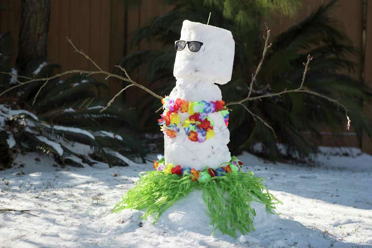 A snowman wearing a grass skirt and flower lei in a yard Tuesday, Feb. 16, 2021 in Spring. Temperatures stayed below freezing Tuesday and roads remained icy.