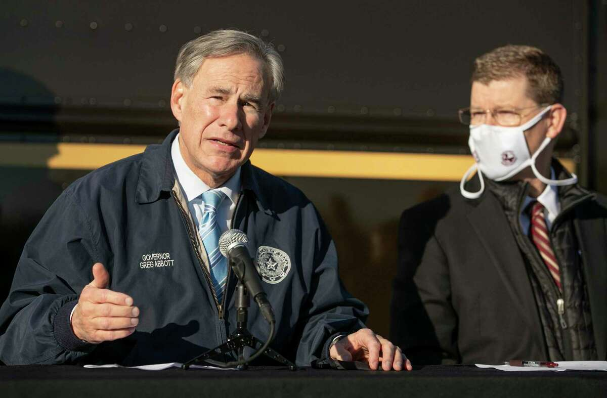 Gov. Greg Abbott talks about the Pfizer-BioNTech COVID-19 vaccine at a UPS Distribution Center in Austin, Texas, on Thursday, Dec. 17, 2020. Listening is Texas Division of Emergency Management Chief Nim Kidd. (Jay Janner/Austin American-Statesman via AP)