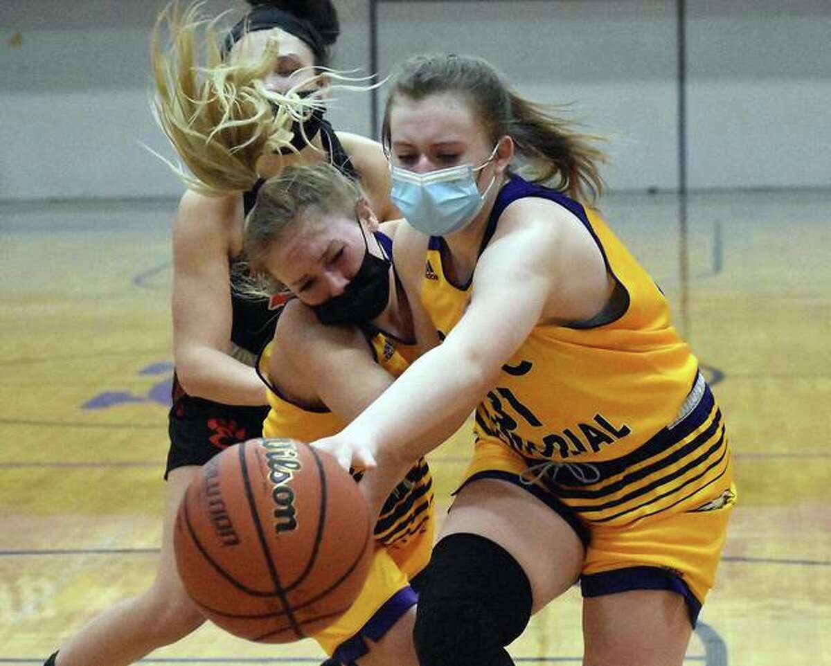 CM's Tori Standefer (left) and Olivia Durbin (right) try to retrieve a loose ball before it goes out of bounds in a game against Edwardsville on Saturday in Bethalto.