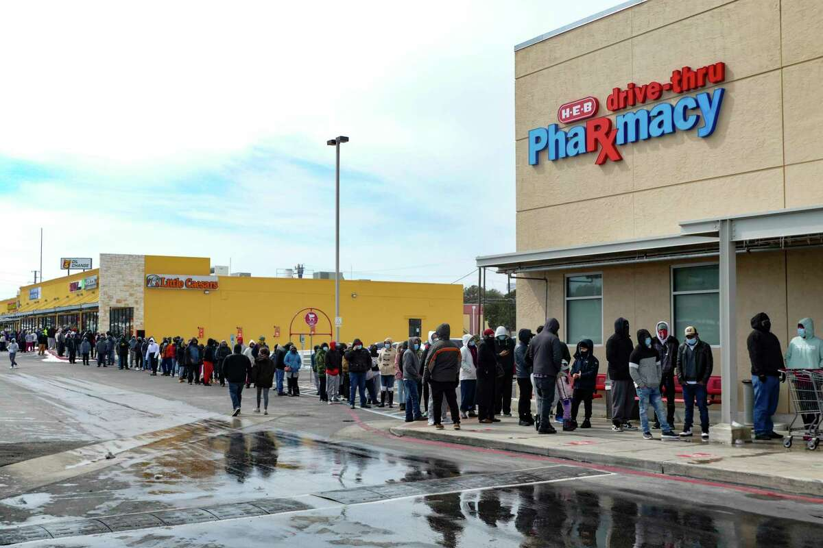 Hundreds of San Antonians stand in line to enter the H-E-B at West Avenue and Blanco Road at noon on Tuesday, Feb. 16, 2021, after snow and freezing temperatures caused the closing the the store chain and most businesses.