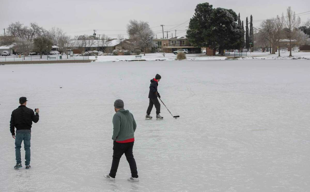 Ben Avary and David Parker walk onto the ice as James Tyrrell, originally from Connecticut, practices his hockey skills as they and other Midlanders venture out onto Wadley Barron Pond 02/16/2021 after the pond froze over. Tim Fischer/Reporter-Telegram