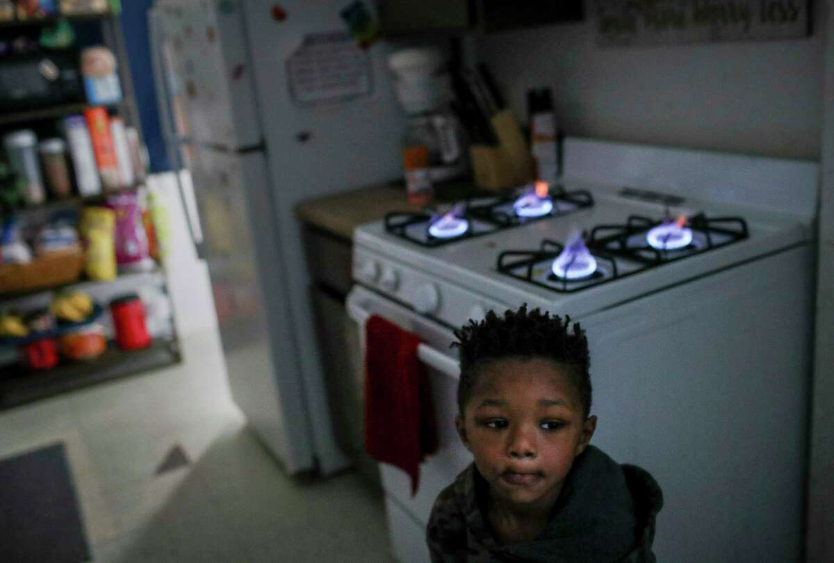 Kaiden Antoine, 3, stands by the stove, his family's only source of heat since their power has been out since yesterday, Tuesday, Feb. 16, 2021, at Cuney Homes in Houston.