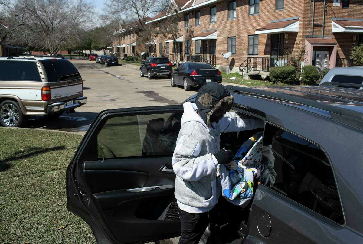Alvin DeCuier loads his son Gavin, 1, into a car to leave their apartment Tuesday, Feb. 16, 2021, at Cuney Homes in Houston. He said their family had been without power since yesterday, and that they all slept in one bed to stay warm last night, as a winter storm hit the Houston area.