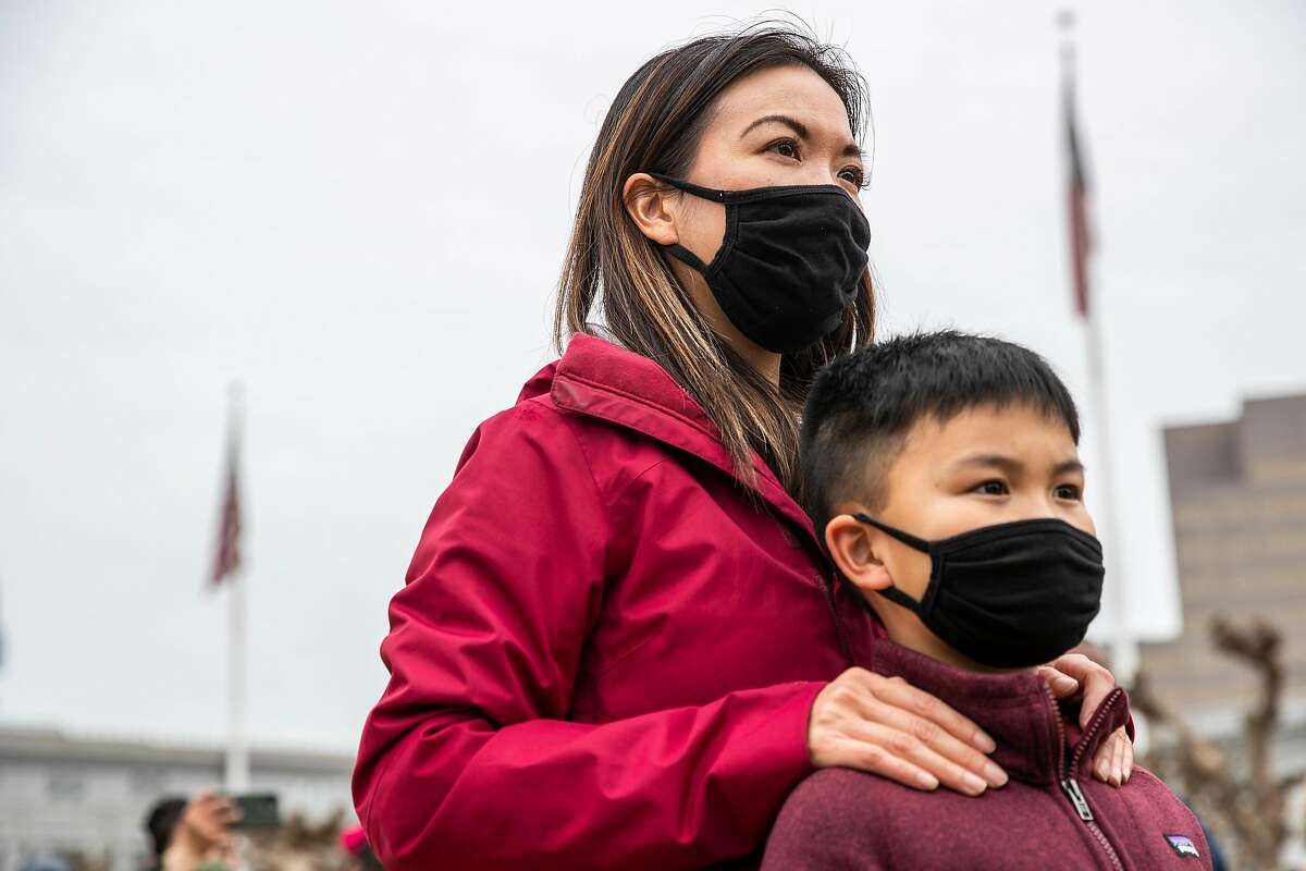 """Minji Wong of San Francisco stands behind her nine-year-old son Miles while attending a """"Love our People: Heal our Communities"""" rally at Civic Center Plaza in condemnation of the recent increase in violence towards the Asian American community around the Bay Area in San Francisco, California Sunday, Feb. 14, 2021."""