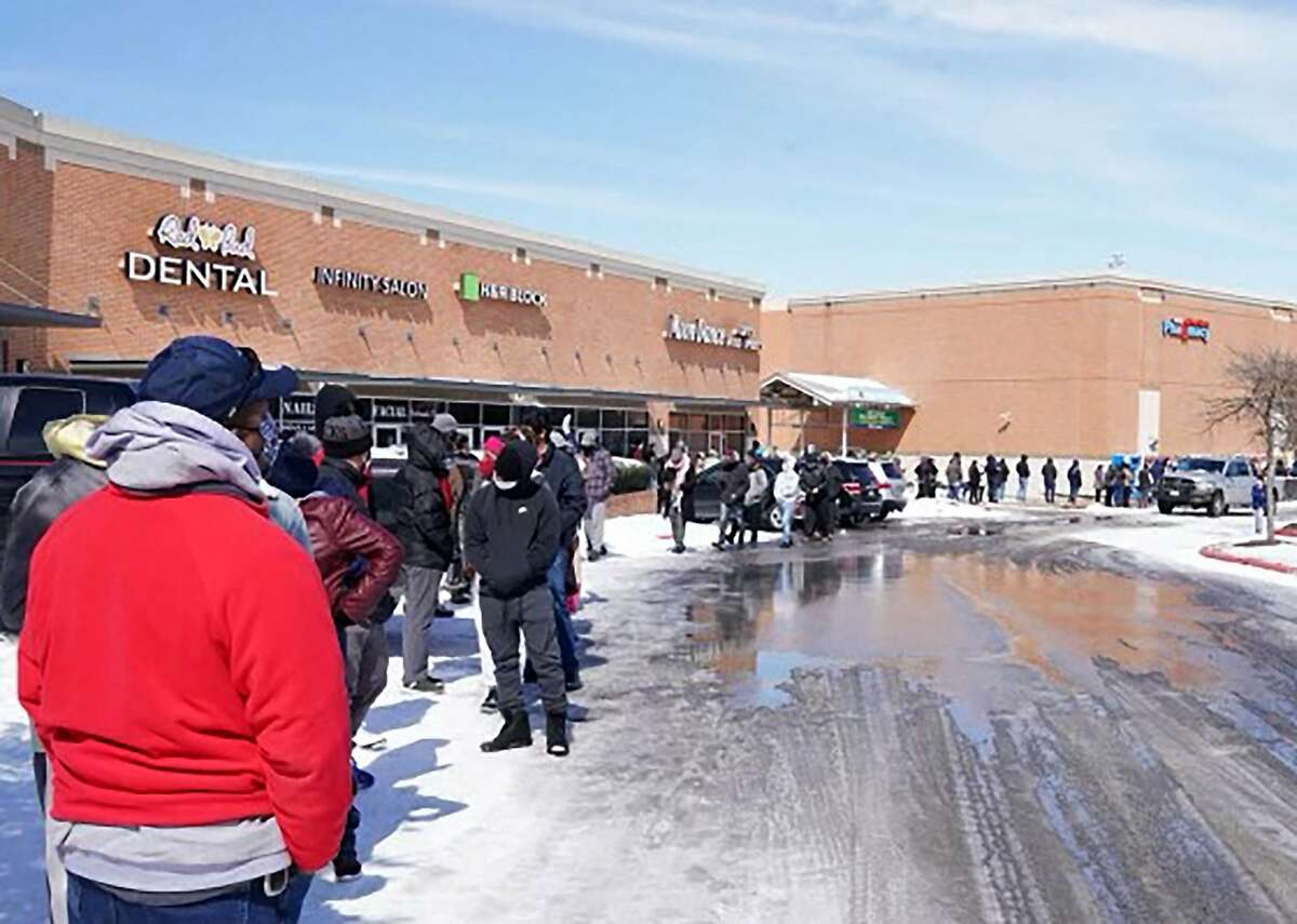 People wait in line at a mall to get inside an H-E-B supermarket in Round Rock, Texas, on February 16, 2021. Millions were left without power as a deadly winter storm gripped the southern and central United States Tuesday. Hardest hit was Texas, where freezing conditions prompted utility companies to implement rotating blackouts to stop the power grid being overloaded by the surge in demand.