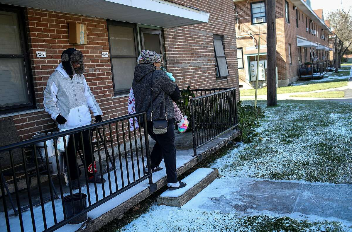 Alvin DeCuier, left, watches as his wife Tamaka Nickson carries their daughter Aayden, 3, to their car to leave their apartment Tuesday, Feb. 16, 2021, at Cuney Homes in Houston. He said their family had been without power since yesterday, and that they all slept in one bed to stay warm last night, as a winter storm hit the Houston area.