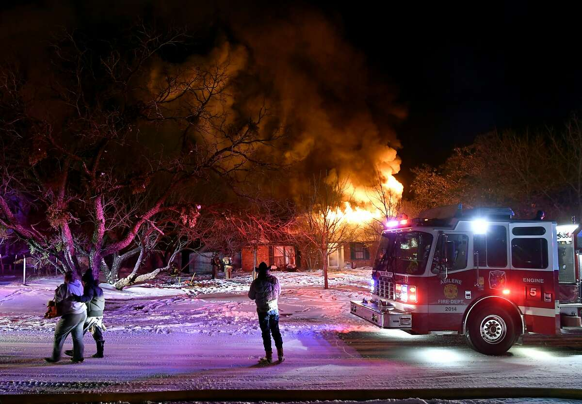 Residents of Cedar Crest Drive walk past their burning house as Abilene, Texas firefighters try to contain the fire Monday Feb. 15, 2021. Crews were only able to draw water from one hydrant because all three city water treatment plants were offline due to power outages. (Ronald W. Erdrich /The Abilene Reporter-News via AP)