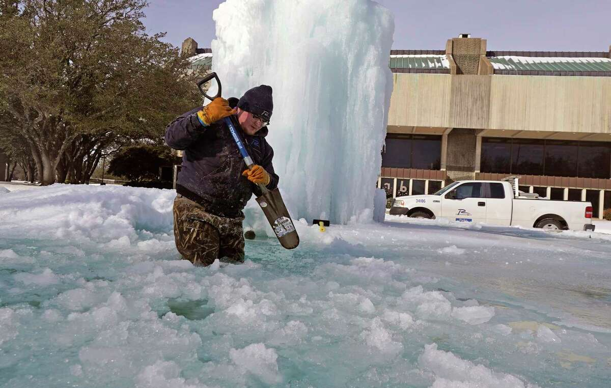 City of Richardson worker Kaleb Love breaks ice on a frozen fountain Tuesday, Feb. 16, 2021, in Richardson, Texas. Temperatures dropped into the single digits as snow shut down air travel and grocery stores.