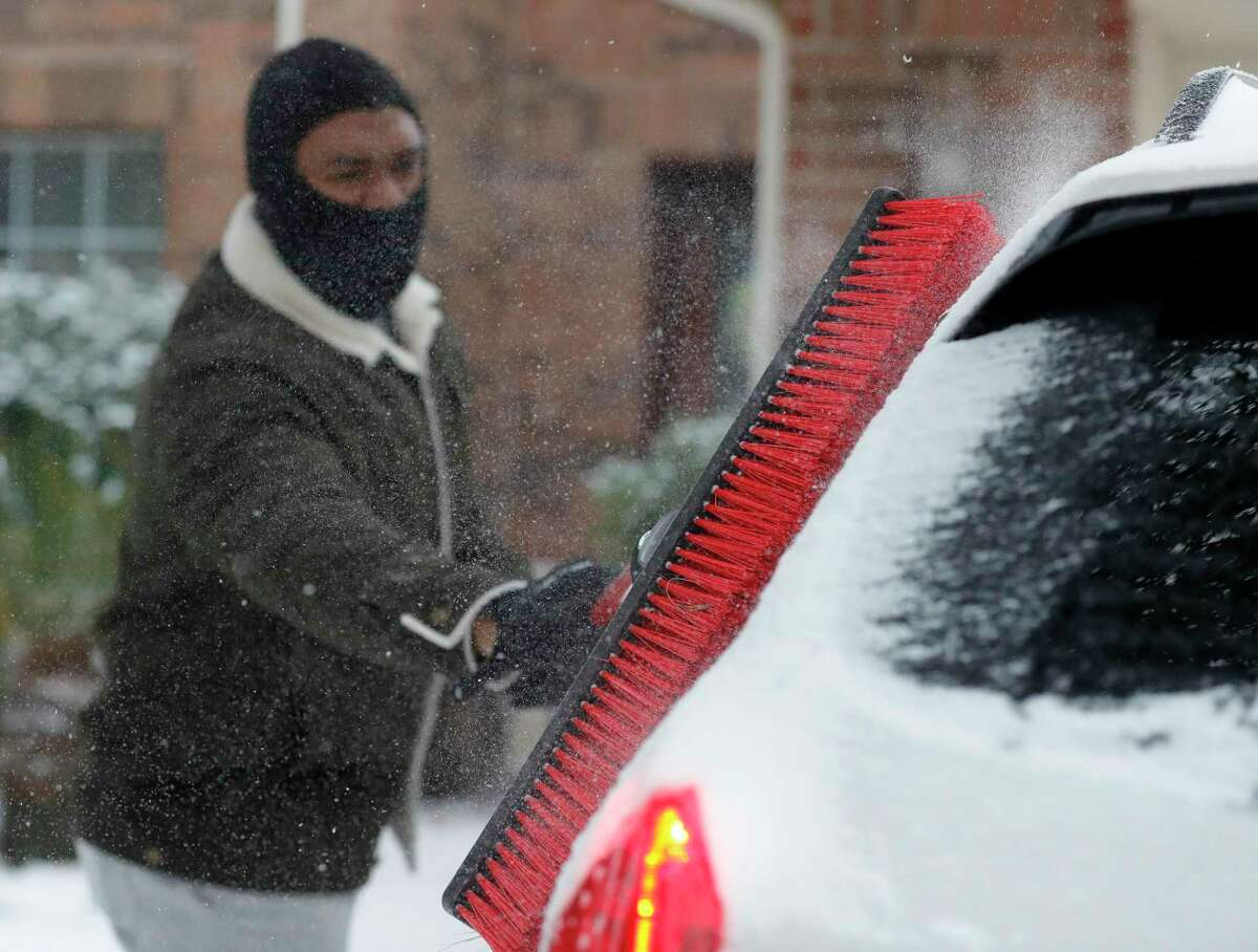 Patrick Minott uses a push broom to scrape snow and ice covered off his vehicles, Monday, Feb. 15, 2021, in Kingwood, Texas. (Jason Fochtman/Houston Chronicle via AP)