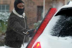 Patrick Minott uses a push broom to scrape snow and ice covered off his vehicles, Monday, Feb. 15, 2021, in Kingwood, Texas. A winter storm making its way from the southern Plains to the Northeast is affecting air travel. (Jason Fochtman/Houston Chronicle via AP)