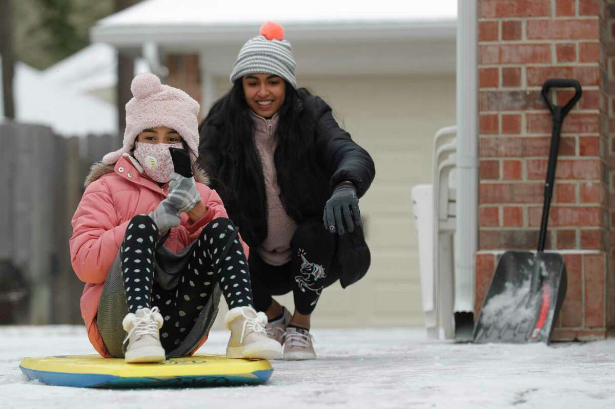 Riva Patel, left, is pused by her older sister, Rahi, down an icy driveway while his other daughter, Rahi, looks on after snow covered homes and roadways through out Greater Houston, Monday, Feb. 15, 2021, in Kingwood.
