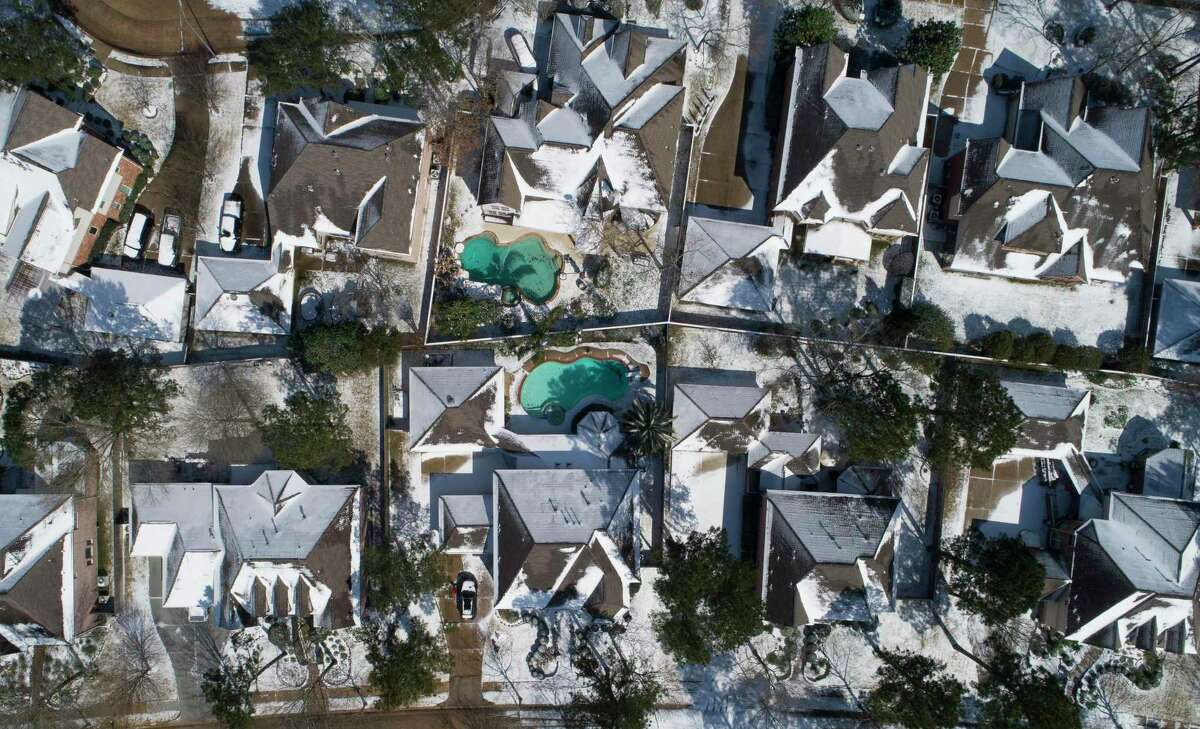 Snow and ice are seen on homes, Monday, Feb. 15, 2021, in Kingwood.