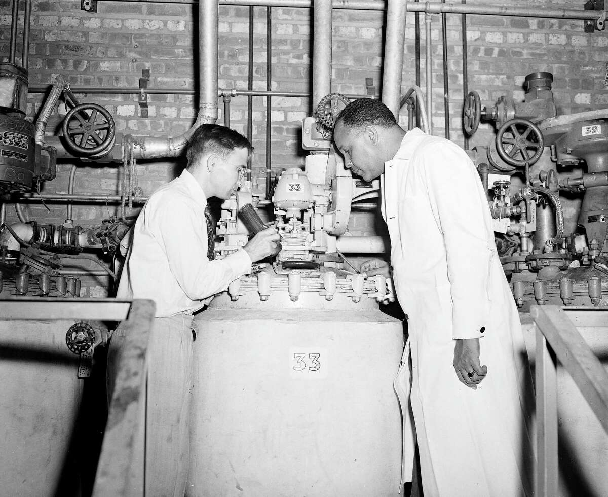 Dr. Percy L. Julian, right, is joined by former student Dr. Arthur Magnani to watch the progress of the manufacture of a hormone product in a tank at the Glidden Co., plant in Chicago, Ill., July 25, 1947. (AP Photo)
