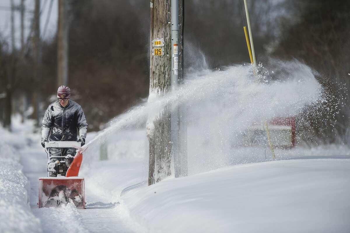 Blake Wanous pushes a snowblower down the sidewalk along Wheeler Street Tuesday, Feb. 16, 2021 in Midland. (Katy Kildee/kkildee@mdn.net)