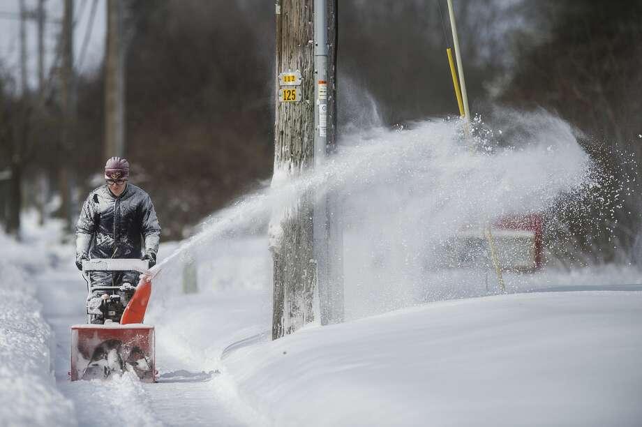 Blake Wanous pushes a snowblower down the sidewalk along Wheeler Street Tuesday, Feb. 16, 2021 in Midland. (Katy Kildee/kkildee@mdn.net) Photo: (Katy Kildee/kkildee@mdn.net)
