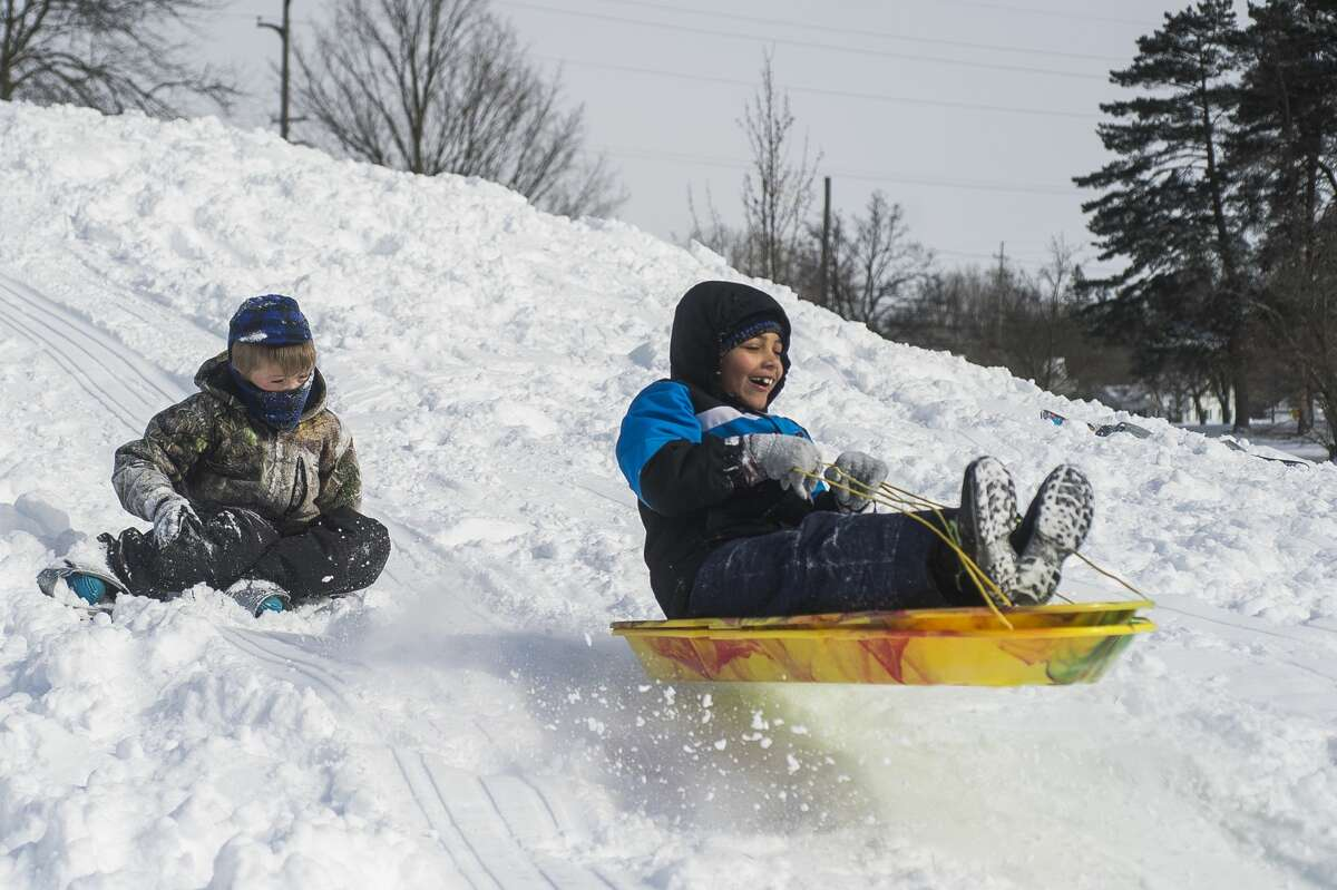 William Stockton, 7, left, and Jeremiah Michner, 8, right, go sledding and snowboarding during a snow day for Midland Public Schools Tuesday, Feb. 16, 2021 at Plymouth Park in Midland. (Katy Kildee/kkildee@mdn.net)