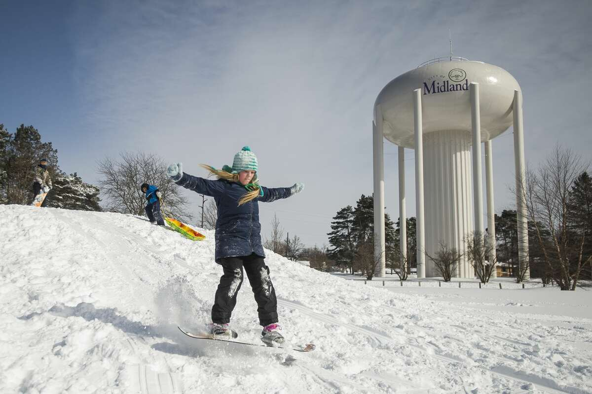 From left, William Stockton, 7, Jeremiah Michner, 8, and Allison Stockton, 12, go sledding and snowboarding during a snow day for Midland Public Schools Tuesday, Feb. 16, 2021 at Plymouth Park in Midland. (Katy Kildee/kkildee@mdn.net)