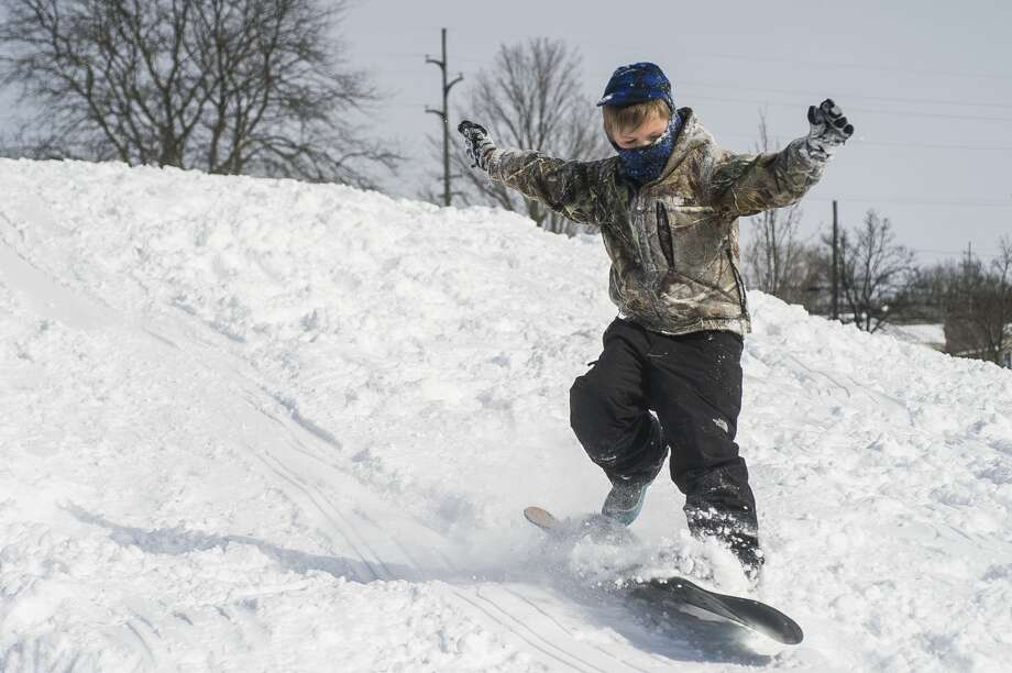William Stockton, 7, goes sledding and snowboarding during a snow day for Midland Public Schools Tuesday, Feb. 16, 2021 at Plymouth Park in Midland. (Katy Kildee/kkildee@mdn.net) Photo: (Katy Kildee/kkildee@mdn.net)