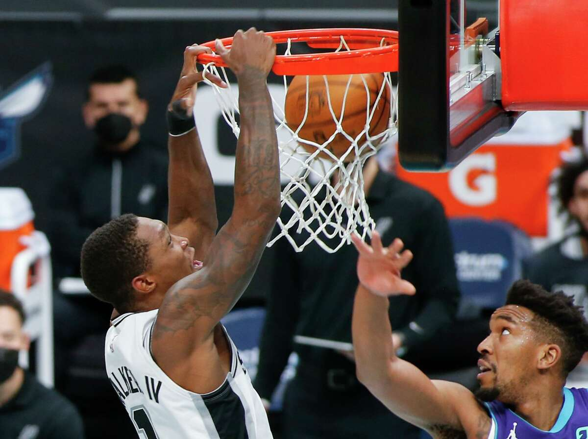Lonnie Walker IV dunks on Charlotte's Malik Monk in the Spurs' 122-110 win Sunday. Walker went 5 of 7 for 11 points and impressed coach Gregg Popovich with his defense.
