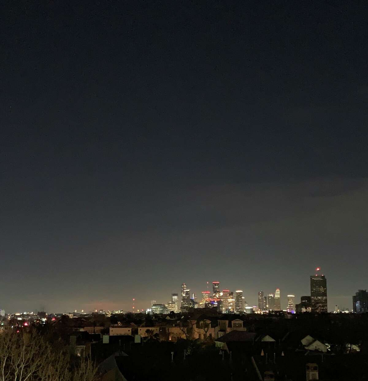 This photo posted on Twitter Monday night shows the Houston skyline lit up brightly while surrounding homes are in the dark.
