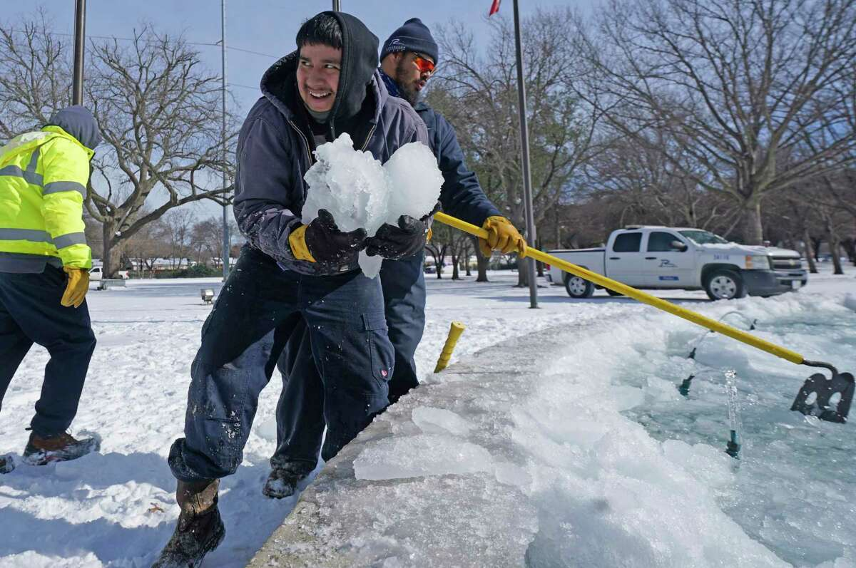City of Richardson workers clear ice from a frozen fountain Tuesday, Feb. 16, 2021, in Richardson, Texas. Temperatures dropped into the single digits as snow shut down air travel and grocery stores.