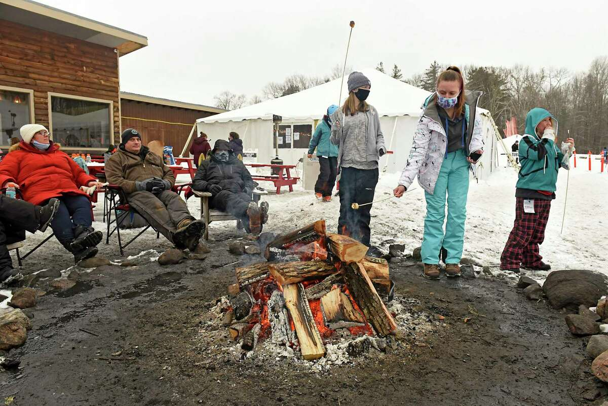 Young skiers toast marshmallows over a bonfire to make s'mores at West Mountain ski area on Monday, Feb. 15, 2021 in Queensbury, N.Y. The mountain is planning a $50 million resort on the northwest base area. (Lori Van Buren/Times Union)