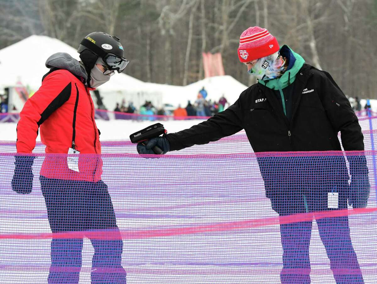 A lift worker scans the pass of a snowboarder at West Mountain ski area on Monday, Feb. 15, 2021 in Queensbury, N.Y. (Lori Van Buren/Times Union)