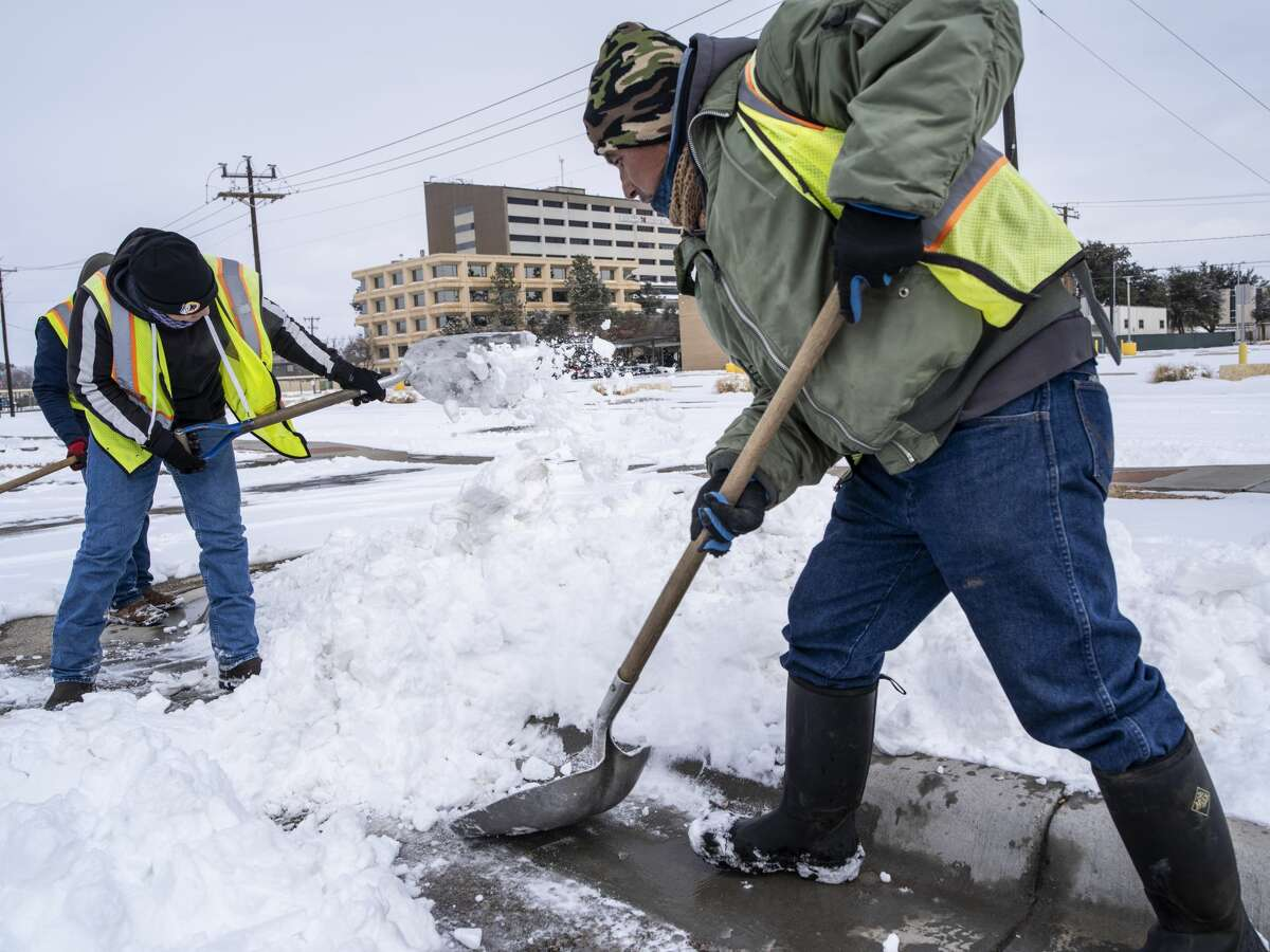 Workers clear snow from a parking lot in Midland, Texas, U.S, on Monday, Feb. 15, 2021. Blackouts triggered by frigid weather have spread to more than four million homes and businesses across the central U.S. and extended into Mexico in a deepening energy crisis that's already crippled the Texas power grid. Photographer: Matthew Busch/Bloomberg