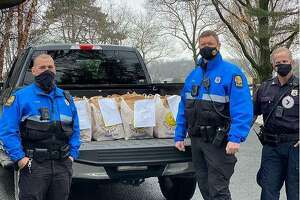 Greenwich police help to distribute food parcels to local families in need after thieves stole parts from vehicles operated by the Transportation Association of Greenwich. The police delivered parcels to 143 families on Tuesday, stepping in to do the work usually handled by TAG.