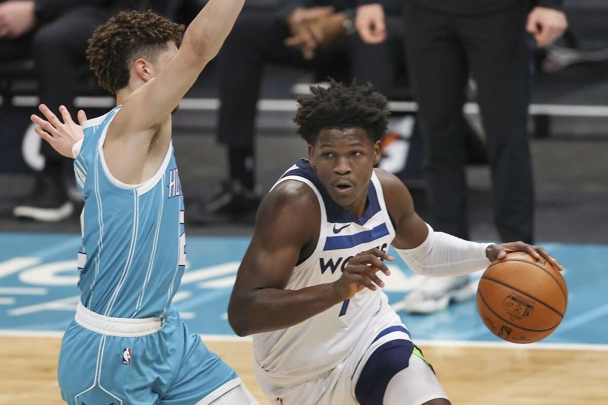 Minnesota Timberwolves forward Anthony Edwards, right, drives past Charlotte Hornets guard LaMelo Ball during the first half of a Feb. 12 game.