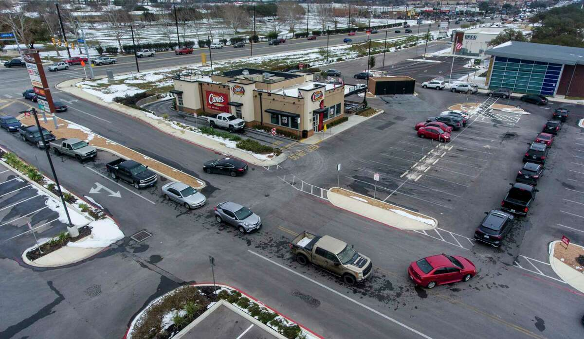 Vehicles encircle a Raising Cane's Chicken Fingers restaurant Tuesday, FEb. 16, 2021 on SE Military Dr. near S. Presa St. With as many as 38 percent of CPS Energy customers without power, long lines formed around the fast food restaurants who had power and were open.