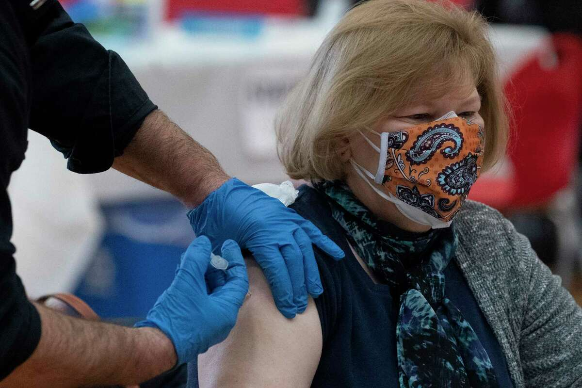 Maryanne Lenhardt gets a COVID-19 vaccination, Wednesday, Feb. 10, 2021, at Central High School in Bridgeport, Conn. The mass vaccination clinic is one of several ways Bridgeport officials are trying to fight the low vaccination rates many cities across the country are seeing compared with wealthier suburbs. (AP Photo/Mark Lennihan)