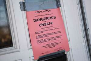A sign is posted declaring the building dangerous and unsafe for human occupancy at North Mianus School in the Riverside section of Greenwich, Conn. Tuesday, Feb. 16, 2021. The ceiling collapsed in part of the building and caused a flood, damaging the building extensively.