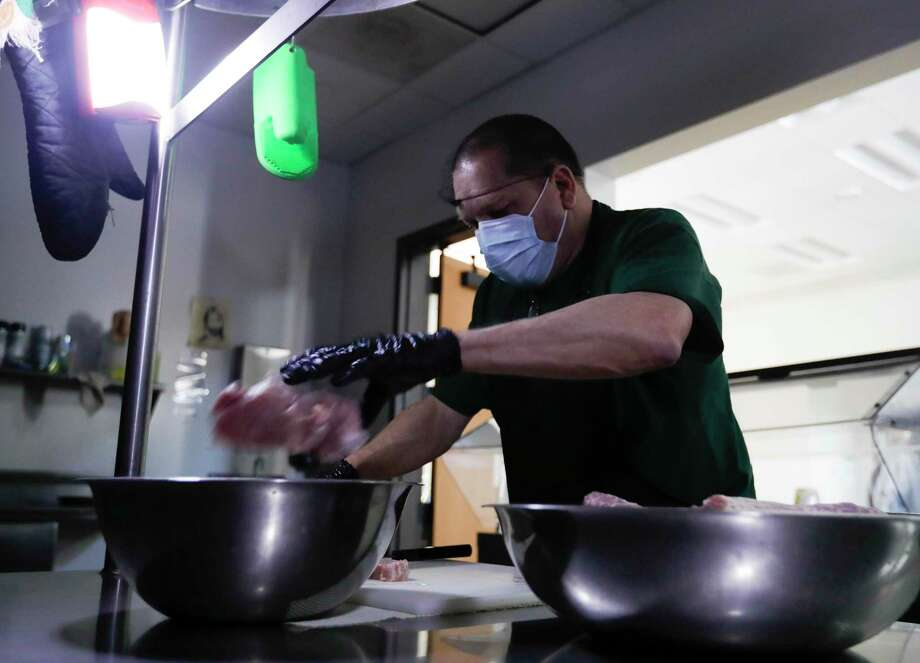 Tom Tucker helps prepare dinner in the dark after the Salvation Army's shelter lost power, Tuesday, Feb. 16, 2021, in Conroe. Photo: Jason Fochtman, Houston Chronicle / Staff Photographer / 2021 © Houston Chronicle