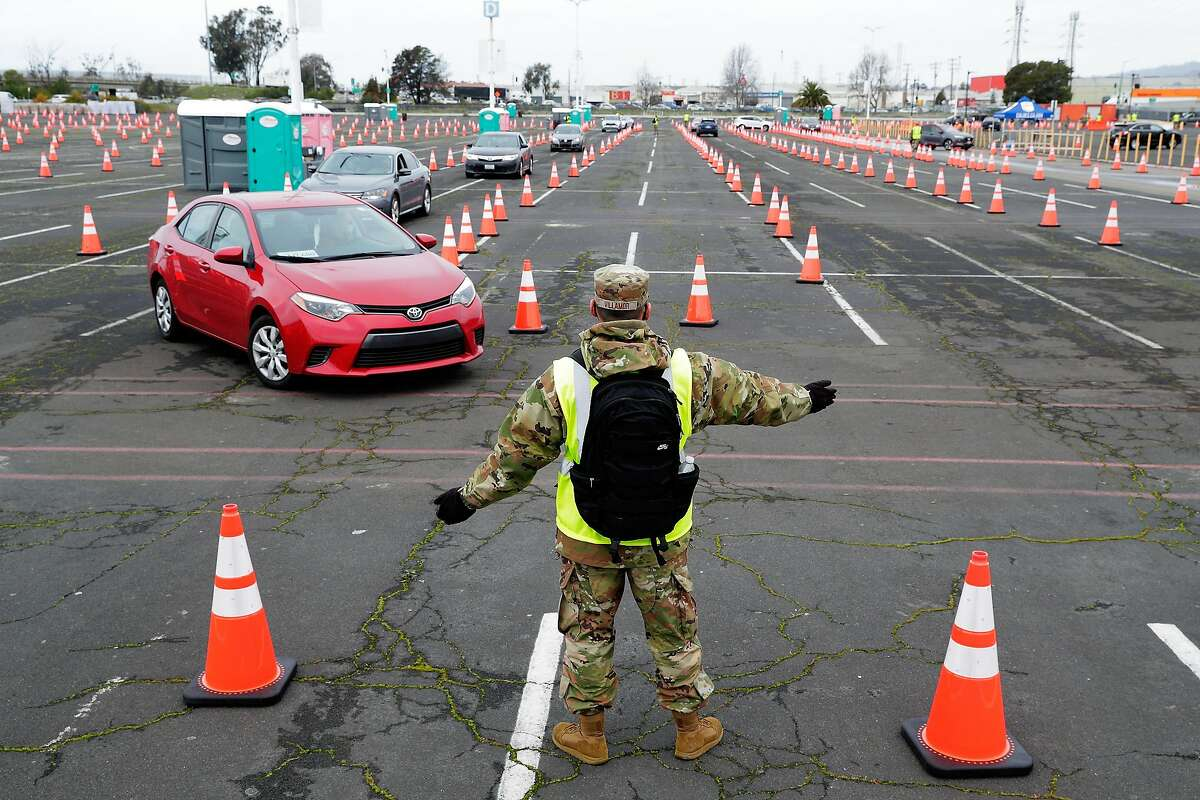 A California National Guard member directs traffic at the newly opened mass vaccination site at the Oakland Coliseum.