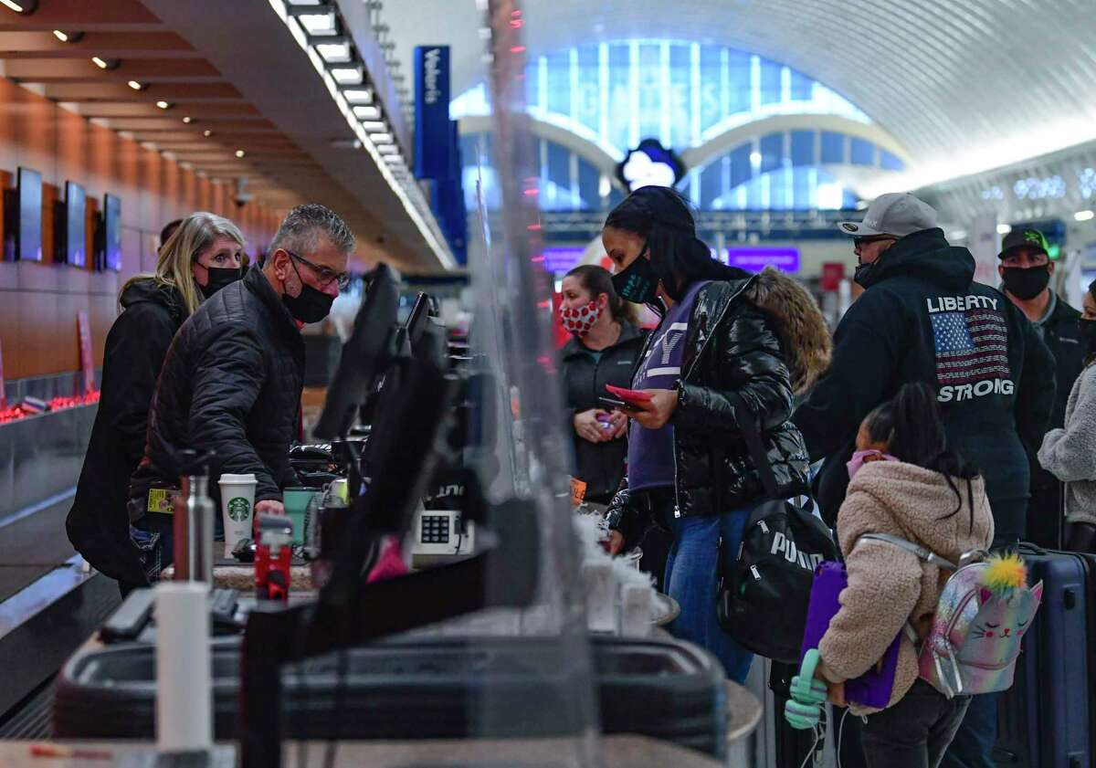 Southwest Airlines personnel attend to customers whose flights have been cancelled after snow fell in San Antonio early on Monday, Feb. 15, 2021. The airport is closed; it lacks sufficient equipment to make the runways and taxiways usable.