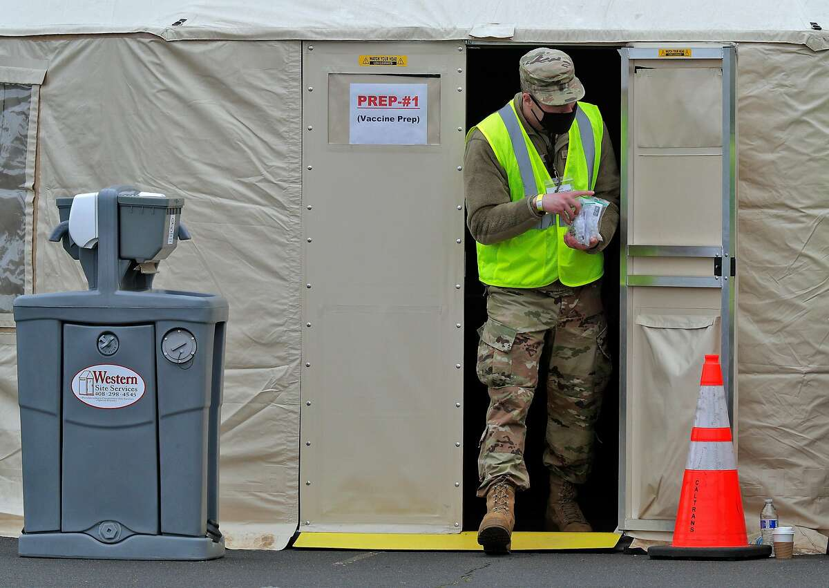 A California National Guard member carries prepped Pfizer COVID-19 vaccines to the healthcare workers as vaccinations were administered to the public for the first day of mass vaccinations at the Oakland Coliseum in Oakland, Calif., on Tuesday, February 16, 2021.