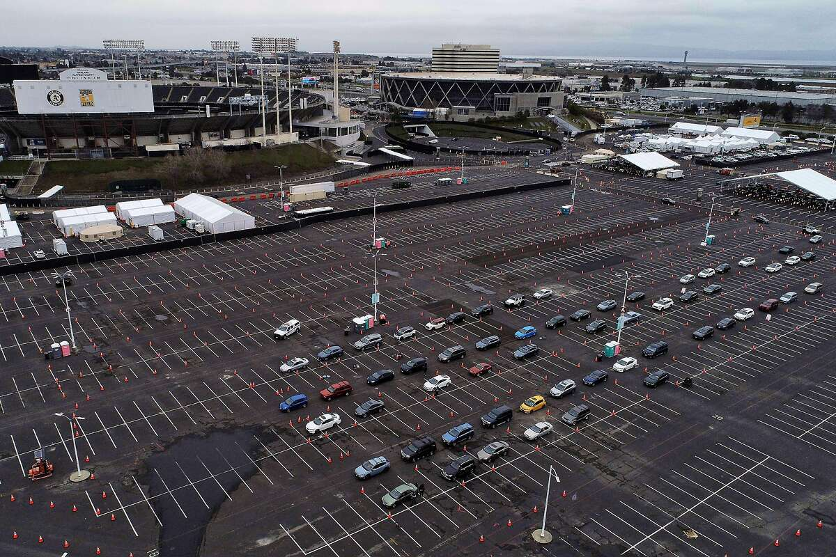 Recipients wait in an observation area in their cars after Pfizer COVID-19 vaccines were administered to the public for the first day of mass vaccinations at the Oakland Coliseum in Oakland, Calif., on Tuesday, February 16, 2021.