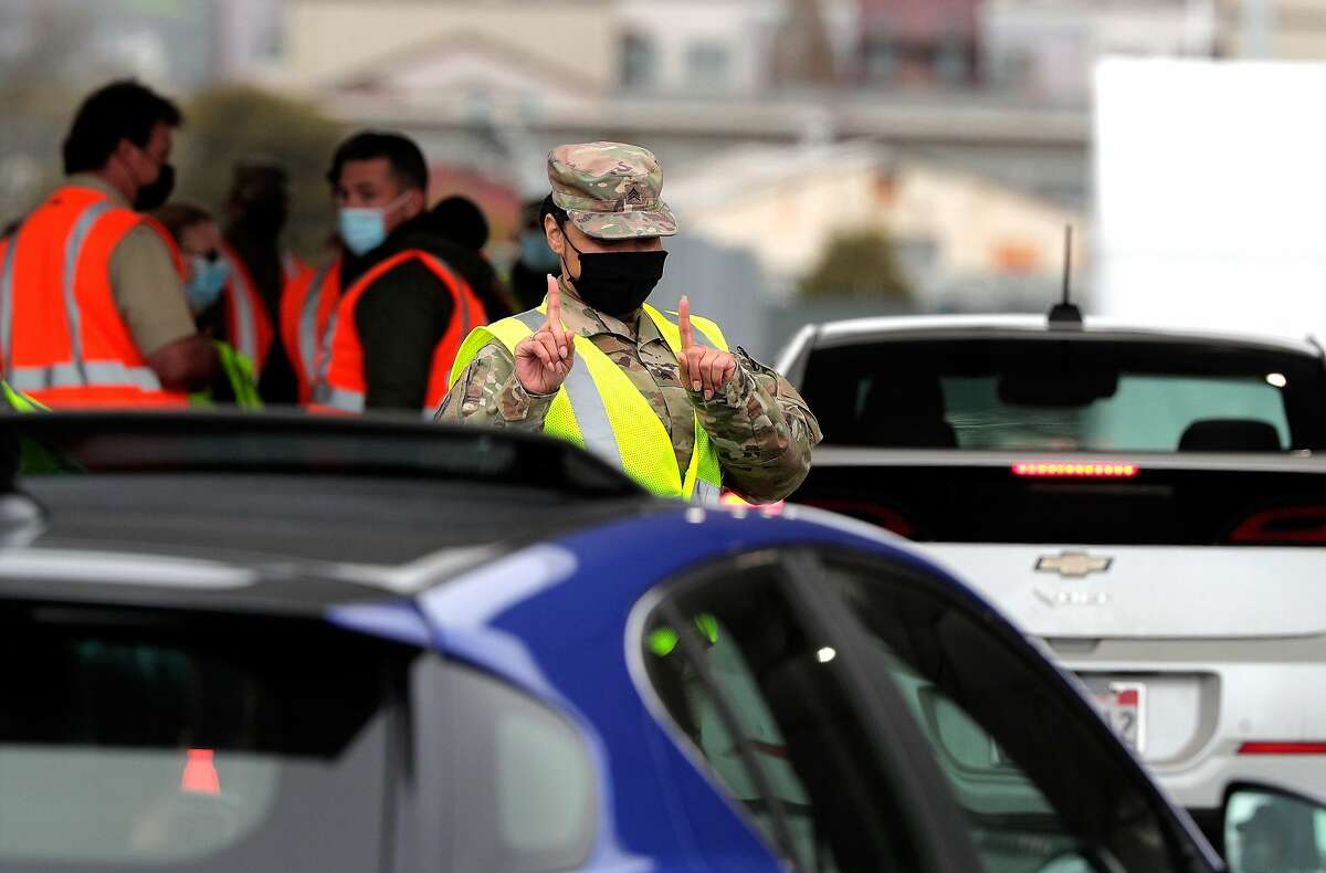 A California National Guard member signals a driver to wait as Pfizer COVID-19 vaccines were administered to the public for the first day of max vaccinations at the Oakland Coliseum in Oakland, Calif., on Tuesday, February 16, 2021.