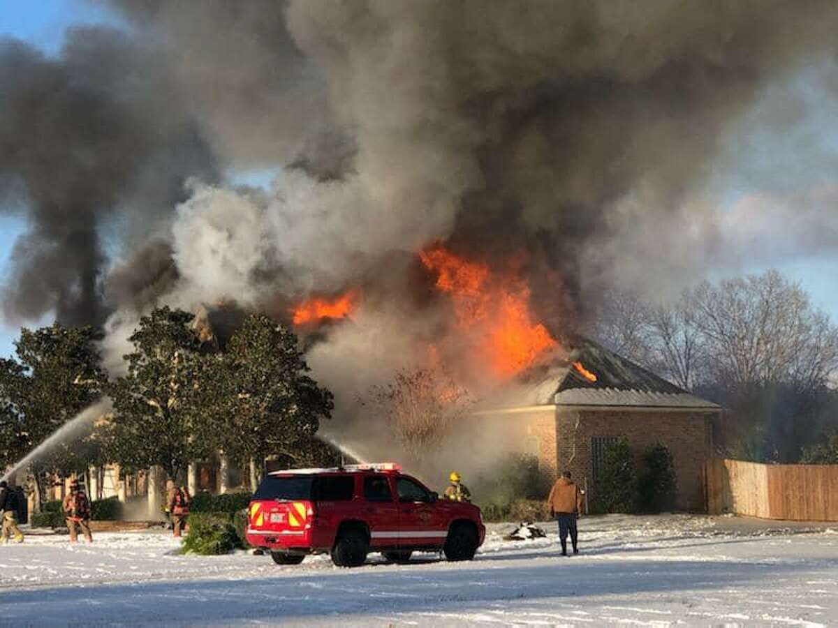 A Montgomery house is seen engulfed in flames on Monday, Feb. 15 as firefighters from the Montgomery, Conroe and Lake Conroe fire departments battle the blaze.
